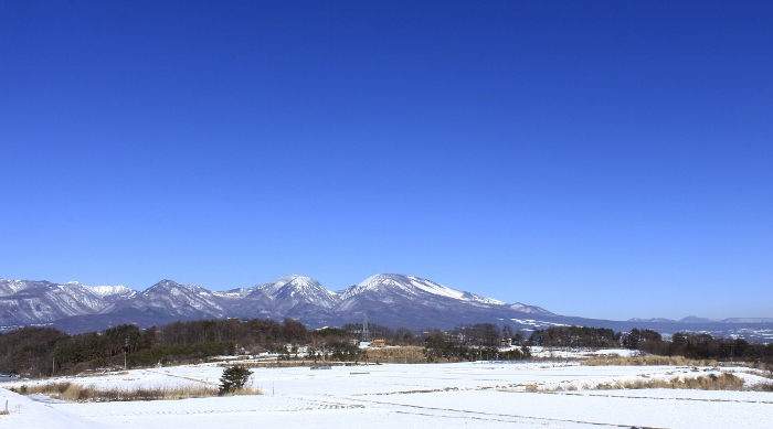 大寒の雪原より望む『そらいろの丘』、右方に広がる佐久平の町